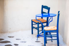 Two blue chairs on a street of typical greek traditional village on Mykonos Island, Greece, Europe Stock Photo