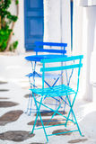 Two blue chairs on a street of typical greek traditional village on Mykonos Island, Greece, Europe Royalty Free Stock Image