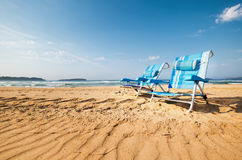 Two blue chaise-longues are on the sand ocean beach Royalty Free Stock Photos