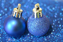 Two blue Christmas balls on blurry background of blue glitter Royalty Free Stock Photos