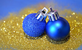 Two blue Christmas balls on golden glitter on blue background Royalty Free Stock Image
