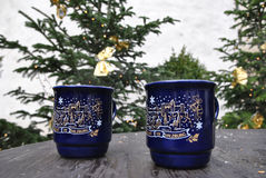 Two blue Christmas mug with an image is on the wooden table. Two blue ceramic Christmas mug with the inscription `Advent in Zalzburg` on a wooden table on the Royalty Free Stock Photography