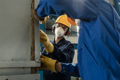 Two blue-collar workers wearing protective equipment. While insulating an industrial pressure vessel Stock Photo