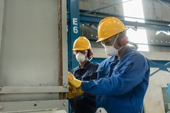 Two blue-collar workers wearing protective equipment. While insulating an industrial pressure vessel Stock Photography