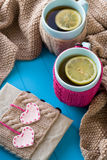 Two blue cup of tea in knitted sweater with hearts felt Royalty Free Stock Image