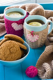 Two blue cup of tea in knitted sweater with hearts felt Stock Images
