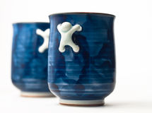 Two blue cups. With crawling men as handles Stock Photography