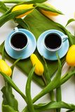 Freshly brewed coffee. Two blue cups of coffee on a table with green cloth and yellow tulips Stock Images