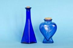 Two blue decorative glass bottle on azure background Royalty Free Stock Photo