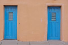 Two blue doors as entrances to a brown stucco building stock images