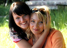 Two blue-eyed girls. The blonde and brunette on the nature. Two smiling girlfriends Stock Photos