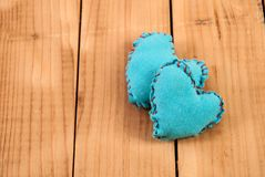 Two blue fabric heart on wood background with space stock images