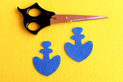 Two blue felt anchor, scissors  on yellow background. Sewing hobby for children, women, beginners. Step. Top view Stock Photography