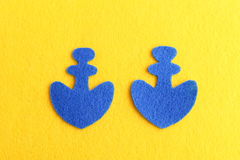 Two blue felt anchor  on yellow background. Sewing crafts for children, women, beginners. Step. Top view. Cut out felt shapes of an anchor. Simple felt DIY Royalty Free Stock Images