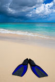 Two blue flippers on the white sand beach Royalty Free Stock Image