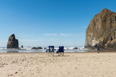 Two blue folding chairs in the sand as a tourist strolls along the beach of Cannon Beach, Oregon, USA. stock image