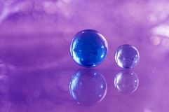 Two blue glass balls on a glass table. Glass balls on a purple background with reflection. Stock Photo