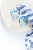 Two blue glass and blue striped napkin on light round wooden boa royalty free stock images