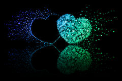 Two blue and green hearts on black background with reflection effect Royalty Free Stock Photo