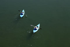 Two blue kayaks on river from above Stock Photos