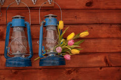 Two blue kerosene lamps with bouquet of tulips on a wooden background. Two blue old kerosene lamps with bouquet of tulips on a wooden background Royalty Free Stock Photography