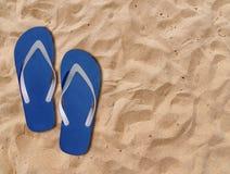 Two blue man lifestyle relax flip flops on orange sandy beach. Close Stock Photos