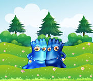 Two blue monsters at the hilltop with pine trees Stock Photography