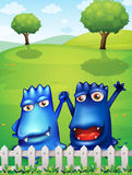 Two blue monsters near the wooden fence Stock Photography
