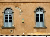 Two blue old windows in Bergamo. Two blue windows in an orange wall of an old building in the Italian historic town of Bergamo in the region of Lombardy. Rough Royalty Free Stock Photography