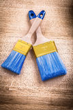 Two blue paint brushes with wooden handles on Royalty Free Stock Images