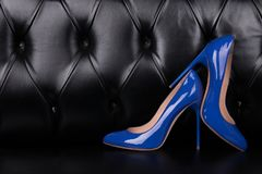 Two blue patent leather shoes on a dark background. Women fashionable high-heeled shoes. High-heeled shoes. Blue shoes on a dark leather background stock image