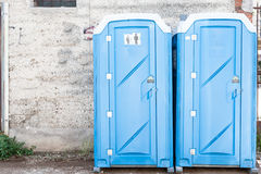 Two blue portable toilet. Two blue portable toilet cabins at construction site Royalty Free Stock Image