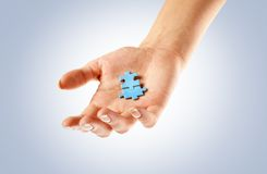 Two blue puzzle pieces on a hand Stock Image