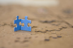 Two Blue Puzzle Pieces. 2 Blue Puzzle Pieces standing on top of blank puzzle, supporting each other stock photo