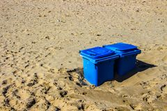 Two blue recycle bins for paper in the sandy dunes in northern holland. royalty free stock photo