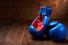 Two blue and red boxing gloves on brown wooden plank against wooden background. Stock Photo