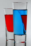 Two blue and red cocktail in full glass with own reflections Stock Photos
