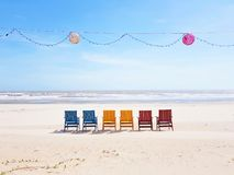 Colourful beach chairs on a wide white sand beach facing the ocean in Vietnam with lampions and a light chain above royalty free stock images