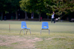 Two blue seats on golf course. Two small blue childrens seats on golf course Royalty Free Stock Images