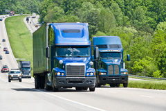Two big blue trucks on a highway. Two big blue trucks travelling on the highway Royalty Free Stock Photography