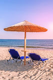 Two blue sunbed, straw umbrella on beautiful beach background in Stock Photos