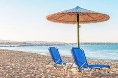 Two blue sunbed, straw umbrella on beautiful beach background. Close Stock Image