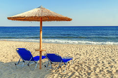 Two blue sunbed, straw umbrella on beautiful beach background Royalty Free Stock Photography