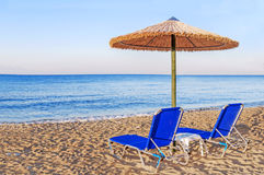 Two blue sunbed, straw umbrella on beautiful beach background Royalty Free Stock Photo
