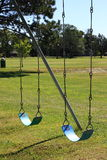 Two Blue Swings. Two blue playground swings sit empty, ready for children to jump on and play Stock Images
