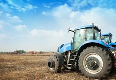 Two blue tractors in the empty field. Royalty Free Stock Photo