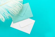 blue and white envelopes and a feather isolated against a blue background. Greeting card concept. Copy space. royalty free stock photos