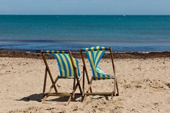 Two blue and white striped beach chairs on the sand beach with its back towards the camera Stock Photo