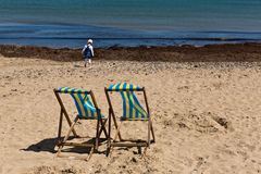 Two blue and white striped beach chairs on the sand beach with its back towards the camera Royalty Free Stock Photos