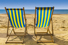 Two blue and yellow deckchairs facing the sea across golden sand Stock Photo